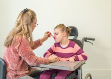 Ένα με ειδικές ανάγκες παιδί σε μια αναπηρική καρέκλα μαζί με έναν εθελοντή εργαζόμενο προσοχής Στοκ Εικόνα