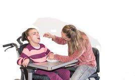 Ένα με ειδικές ανάγκες παιδί σε μια αναπηρική καρέκλα μαζί με έναν εθελοντή εργαζόμενο προσοχής Στοκ φωτογραφία με δικαίωμα ελεύθερης χρήσης