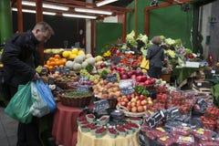 Ένα μη αναγνωρισμένο άτομο αγοράζει τα φρούτα και λαχανικά σε έναν στάβλο στην αγορά δήμων Στοκ Φωτογραφίες