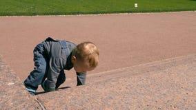 Ένα μικρό αγοράκι που αναρριχείται επάνω στα σκαλοπάτια πετρών απόθεμα βίντεο