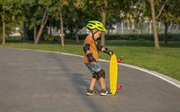 Ένα μικρό αγόρι απολαμβάνει μια κίτρινη πένα ταχύπλοων σκαφών plastboard στοκ φωτογραφία με δικαίωμα ελεύθερης χρήσης