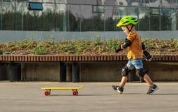 Ένα μικρό αγόρι απολαμβάνει μια κίτρινη πένα ταχύπλοων σκαφών plastboard στοκ φωτογραφία