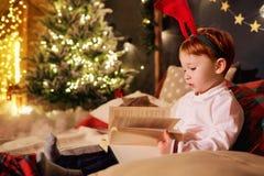 Ένα μικρό αγόρι διαβάζει ένα βιβλίο στο δωμάτιο Χριστουγέννων Στοκ Εικόνα