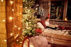 Ένα μικρό αγόρι διαβάζει ένα βιβλίο στο δωμάτιο Χριστουγέννων Στοκ φωτογραφίες με δικαίωμα ελεύθερης χρήσης