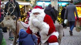 Ένα μικρό αγόρι είναι ευτυχές να καθίσει στην περιτύλιξη Santa ` s στην έκθεση Χριστουγέννων απόθεμα βίντεο