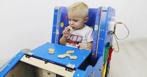 Ένα μικρό αγόρι κάθεται σε ένα αυτοκίνητο ανάπτυξης και τρώει τα μπισκότα απόθεμα βίντεο