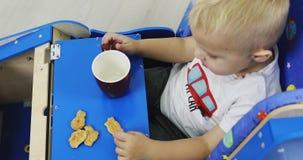 Ένα μικρό αγόρι κάθεται σε busycar του και τρώει τα μπισκότα και πίνει το τσάι απόθεμα βίντεο