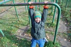 Ένα μικρό αγόρι κρεμά στο φραγμό, εξετάζει μας και χαμογελά στοκ φωτογραφίες