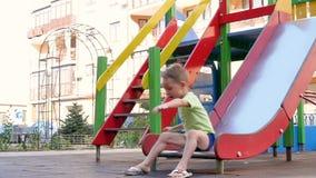 Ένα μικρό αγόρι κυλά κάτω μια φωτογραφική διαφάνεια στην παιδική χαρά δοκιμάζοντας τις συγκινήσεις φιλμ μικρού μήκους