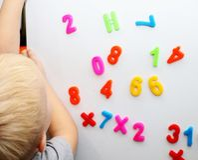 Ένα μικρό αγόρι μελετά τους μαγνητικούς αριθμούς στο ψυγείο Κατάρτιση Preschooler στοκ φωτογραφίες