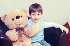 Ένα μικρό αγόρι με ένα Teddy αντέχει Στοκ Εικόνες