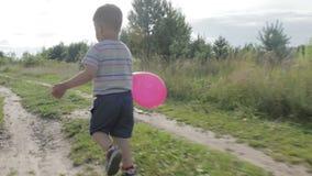 Ένα μικρό αγόρι με ένα μπαλόνι απόθεμα βίντεο
