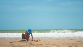 Ένα μικρό αγόρι παίζει στην άμμο στη θάλασσα, τα μικρά πόδια και τα δάχτυλα, ένα υπόβαθρο της κίτρινης άμμου θάλασσας και το μπλε φιλμ μικρού μήκους