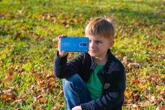 Ένα μικρό αγόρι παίρνει τις εικόνες στο τηλέφωνο στο πάρκο μια ηλιόλουστη ημέρα στοκ φωτογραφία με δικαίωμα ελεύθερης χρήσης