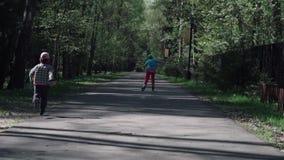 Ένα μικρό αγόρι πιάνει το κορίτσι που οδηγά στα σαλάχια κυλίνδρων Αργός-Mo φιλμ μικρού μήκους