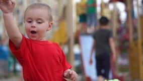 Ένα μικρό αγόρι ρίχνει μακριά ένα μανταρίνι όπως μια σφαίρα στην παιδική χαρά σε σε αργή κίνηση απόθεμα βίντεο