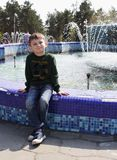 Ένα μικρό αγόρι σε ένα πράσινο πουλόβερ κάθεται κοντά σε μια μεγάλη πηγή στο πάρκο και εξετάζει τη κάμερα στοκ φωτογραφία με δικαίωμα ελεύθερης χρήσης