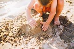 Ένα μικρό αγόρι στηρίζεται τους αριθμούς από την άμμο στην ακτή της λίμνης στο ηλιοβασίλεμα της ημέρας, τα χέρια σκάβουν επάνω τη Στοκ φωτογραφία με δικαίωμα ελεύθερης χρήσης