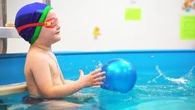 Ένα μικρό αγόρι στη λίμνη πιάνει μια μπλε σφαίρα Το ρίχνει στα κολυμπώντας προστατευτικά δίοπτρά του φιλμ μικρού μήκους