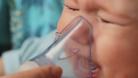 Ένα μικρό αγόρι φωνάζει όταν mom βάζει σε μια inhaler μάσκα στο πρόσωπό του Επεξεργασία του βήχα Διαδικασία της εισπνοής φιλμ μικρού μήκους