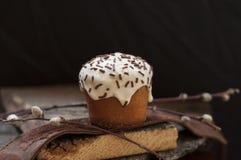 Ένα μικρό κέικ Πάσχας και ένας κλαδίσκος ιτιών σε ένα σκοτεινό ξύλινο υπόβαθρο Στοκ Εικόνες