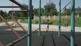 Ένα μικρό κορίτσι έντυσε στα προστατευτικά τρεξίματα αθλητικού εξοπλισμού μεταξύ του αθλητικού εξοπλισμού στην παιδική χαρά πόλεω φιλμ μικρού μήκους