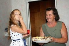 Ένα μικρό κορίτσι δοκιμάζει ένα κέικ από το χέρι της από το πιάτο στοκ φωτογραφίες με δικαίωμα ελεύθερης χρήσης