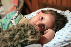 Ένα μικρό κορίτσι είναι στο κρεβάτι με το παιχνίδι πριν από τον ύπνο στοκ εικόνες