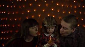 Ένα μικρό κορίτσι εκρήγνυται ένα κερί σε ένα εορταστικό κέικ με το mom και τον μπαμπά της απόθεμα βίντεο