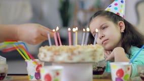 Ένα μικρό κορίτσι εξετάζει ένα κέικ με τα κεριά και λυπημένος φιλμ μικρού μήκους