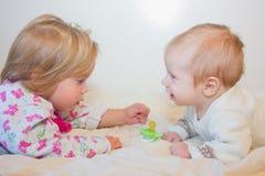 Ένα μικρό κορίτσι εξετάζει το μωρό απομονωμένο λευκό αδελφών ανασκόπησης αδελφός Μωρά και στοκ φωτογραφία με δικαίωμα ελεύθερης χρήσης