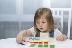 Ένα μικρό κορίτσι θυμάται τις γεωμετρικές μορφές Πρόωρη κατακόρυφος εκπαίδευσης Στοκ Φωτογραφία