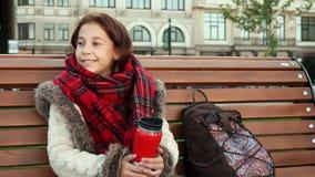 Ένα μικρό κορίτσι κάθεται σε έναν πάγκο σε μια μεγάλη πόλη φιλμ μικρού μήκους