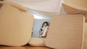 Ένα μικρό κορίτσι κάθεται σε ένα προσωρινό σπίτι των μαξιλαριών και ένα γενικό σπίτι απόθεμα βίντεο