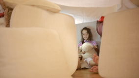 Ένα μικρό κορίτσι κάθεται σε ένα προσωρινό σπίτι των μαξιλαριών και ένα γενικό σπίτι φιλμ μικρού μήκους
