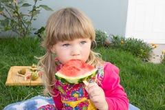 Ένα μικρό κορίτσι κάθεται στη χλόη και τρώει ένα καρπούζι στοκ εικόνες