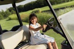 Ένα μικρό κορίτσι κάθεται στο κάθισμα οδηγών ` s στο αυτοκίνητο γκολφ Στοκ Φωτογραφία