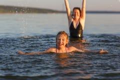 Ένα μικρό κορίτσι και η μητέρα της στο νερό της θάλασσας Στοκ Εικόνες