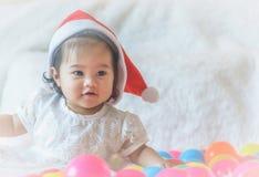 Ένα μικρό κορίτσι, ένα καπέλο Άγιου Βασίλη, παίζει στο κρεβάτι και το colo της στοκ φωτογραφίες
