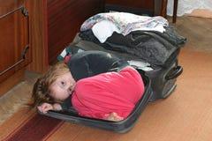 Ένα μικρό κορίτσι κατσάρωσε επάνω στο καπάκι μιας βαλίτσας που γέμισαν με τα πράγματα στοκ εικόνες
