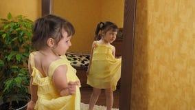 Ένα μικρό κορίτσι κοιτάζει στον καθρέφτη Ένα όμορφο κορίτσι με τις ουρές στο κεφάλι της κρατά το φόρεμά της Ένα παιδί στο α φιλμ μικρού μήκους