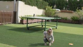 Ένα μικρό κορίτσι κτυπά μια σφαίρα με μια ρακέτα αντισφαίρισης απόθεμα βίντεο