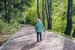 Ένα μικρό κορίτσι με έναν κλάδο σε την παραδίδει ένα πράσινο πάρκο στοκ εικόνες