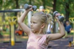 Ένα μικρό κορίτσι με τα ξανθά μαλλιά πηγαίνει μέσα για τον αθλητισμό Το παιδί στο χώρο αθλήσεων αυξάνει τους αλτήρες στοκ φωτογραφίες