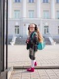 Ένα μικρό κορίτσι με τις κόκκινες ουρές ενώπιον του σχολείου, εξετάζει τη κάμερα στοκ εικόνα