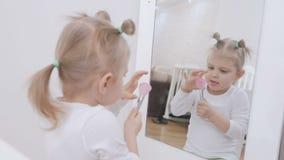 Ένα μικρό κορίτσι μπροστά από έναν καθρέφτη ισχύει makeup στο πρόσωπό της με μια βούρτσα χαριτωμένο κορίτσι λίγο πορτρέτο απόθεμα βίντεο