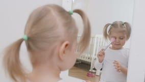 Ένα μικρό κορίτσι μπροστά από έναν καθρέφτη ισχύει makeup στο πρόσωπό της με μια βούρτσα χαριτωμένο κορίτσι λίγο πορτρέτο φιλμ μικρού μήκους