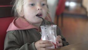 Ένα μικρό κορίτσι πίνει ένα κοκτέιλ γάλακτος βανίλιας σε έναν καφέ απόθεμα βίντεο