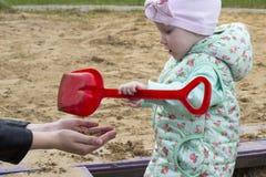Ένα μικρό κορίτσι παίζει στο Sandbox με το mom της, κλείνει επάνω το φθινόπωρο στοκ εικόνα