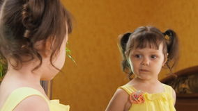 Ένα μικρό κορίτσι παρουσιάζει γλώσσα της στον καθρέφτη Ένα όμορφο κορίτσι με τις ουρές στο κεφάλι της χτίζει τα πρόσωπα της ανταν απόθεμα βίντεο